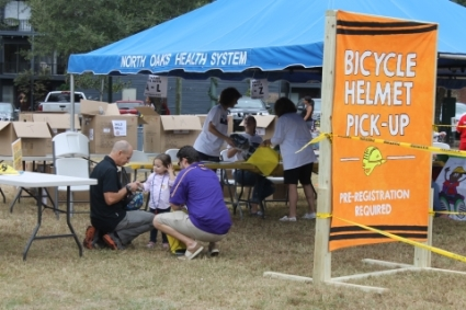 people outside under a tent at a bicycle helmet pick-up